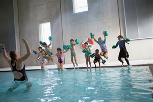 Barn hoppar ner i en simbassäng.