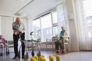 Två personer spelar bowling inne på ett vård- och omsorgsboende.