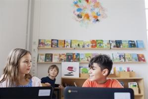 Tre barn i ett klassrum.